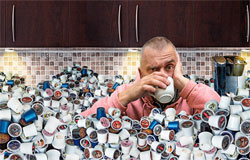 Coffee pod drinker surrounded by used coffee pod waste